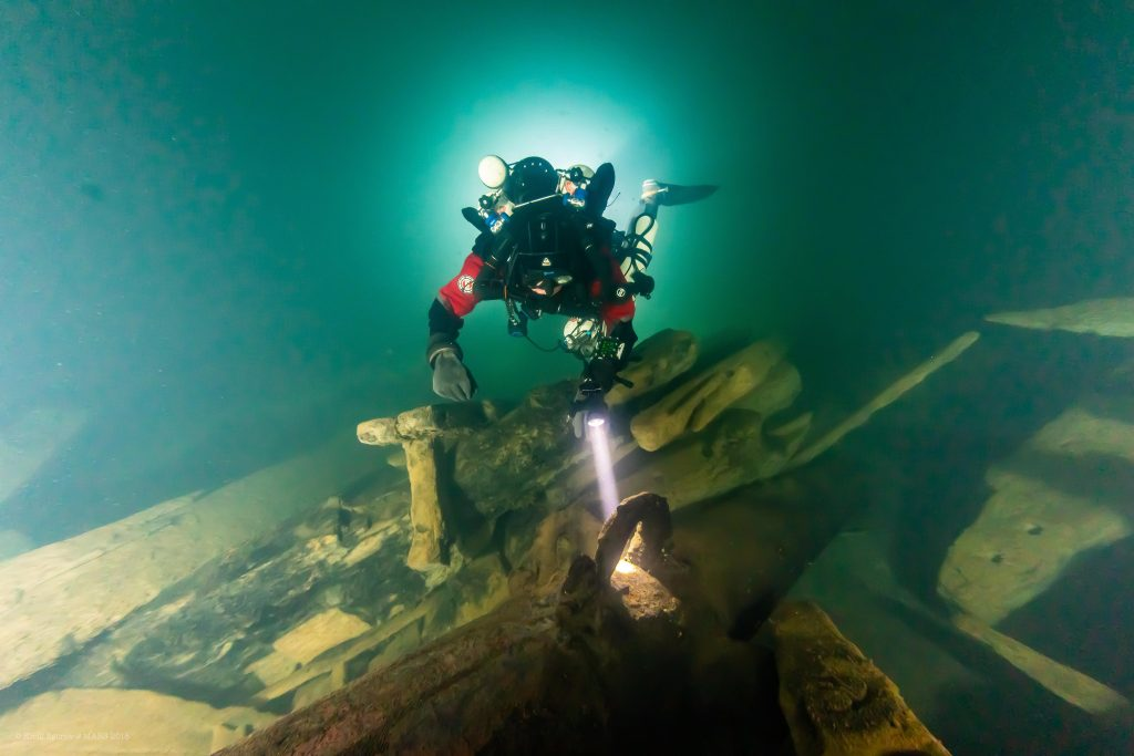 Diver swimming along the remains of the warship, the Mars.
